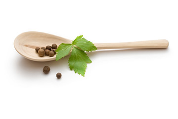 Pepper in a wooden spoon and parsley