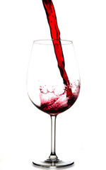 Pouring red wine into glass, isolated on white background