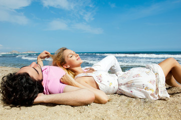 Young couple lying together on a sand by sea and looking to a sk