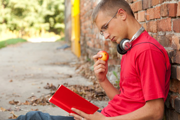 male student with book, leaning on the bricks wall