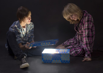 Portrait of  two teenagers looking in a magic lighting box