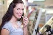 Cute brunette buying cosmetics. Applying lipstick in a drugstore
