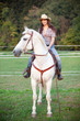 Beautiful cowgirl riding a white horse