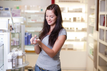 Happy young woman buying a perfume. Shallow DOF.