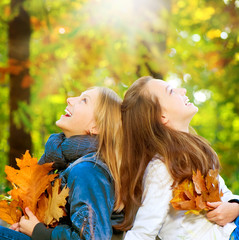 Beautiful Teenage Girls having fun in Autumn Park. Outdoor