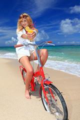 波打ち際で自転車に乗りオレンジジュースを持っている女性