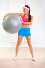 Full length portrait of smiling girl holding fitness ball