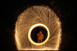 person in a ring burning steel in a dark tunnel