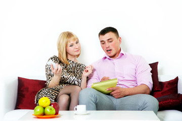 Happy couple sitting at sofa at home, planning something