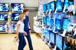 Young couple in electronics store looking at TVs