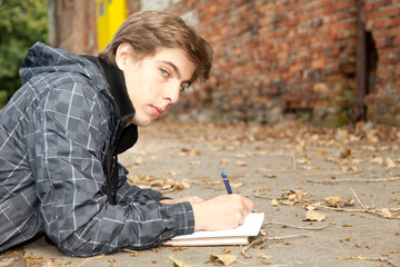lying male student learning by the wall in park