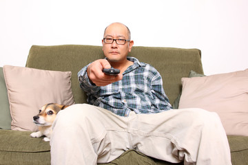 Asian man with remote watching television.
