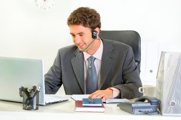 Smiling modern manager with headset looking in laptop