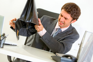 Businessman trying shakes out everything from suitcase