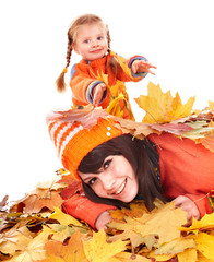 Happy family with child on autumn orange leaves.