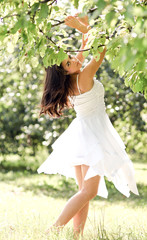 Portrait of beautiful cute young girl yearning in leafage outdoo