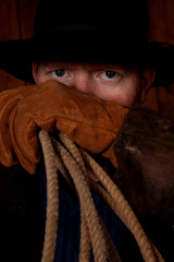Cowboy looking over glove with rope