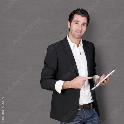 Smiling man standing on dark background