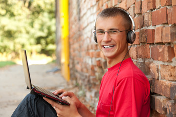 male student working on laptop, sitting near the wall