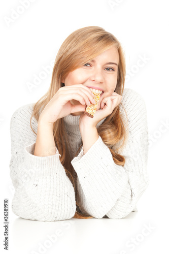 beautiful young woman eating bar with cereals