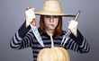 Funny girl in cap and fork with knife try to eat a pumpkin.