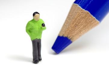 メールを打つ人と青い鉛筆