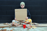 Beggar with blank cardboard sign