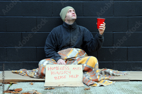 Young man begs on sidewalk