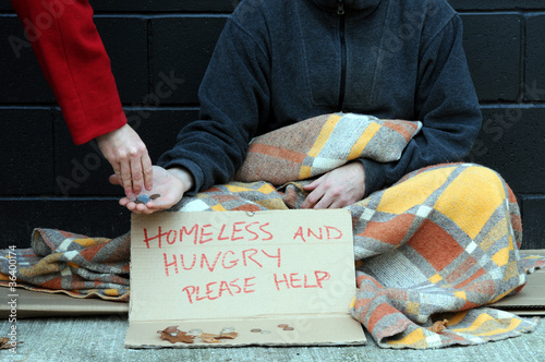 Woman gives change to begging man on street