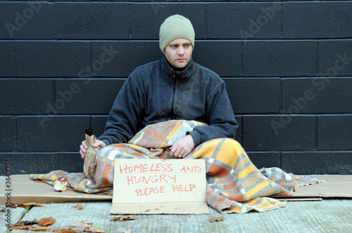 Young homeless man begs on sidewalk