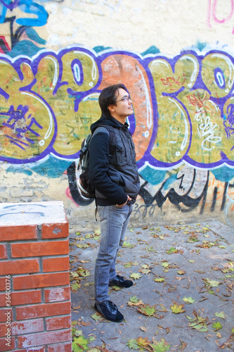 Young man in front of graffiti wall