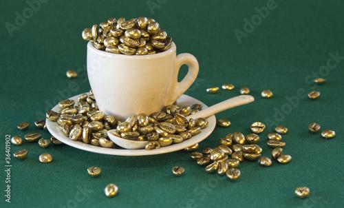 tazzina con chicchi di caffè dorati