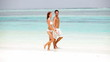 Portrait of carefree couple enjoying while walking on seashore