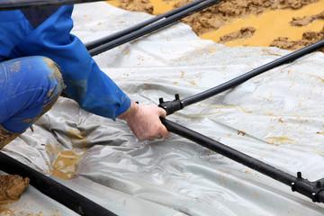 Handwerker installiert Erdwärmerohre im Boden