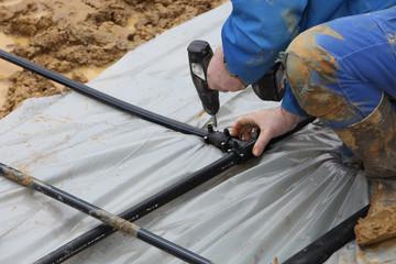 Handwerker verbindet Erdwärme-Rohre im Erdreich