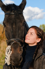 portrait of a pretty young woman with a black horse