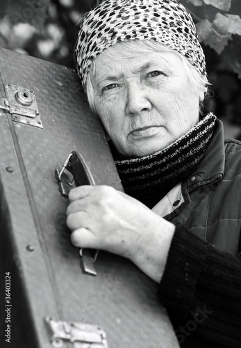 Elderly woman with old suitcase
