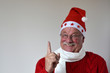 Lachender Weihnachtsmann zeigt mit Finger nach oben