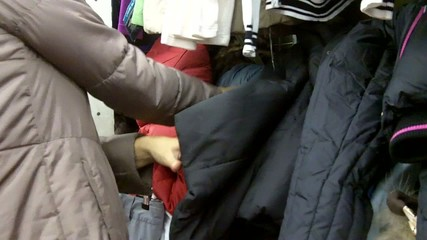 Woman chooses clothes in shop