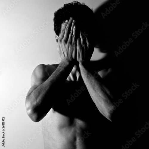 Portrait of a young man covering his face in hands