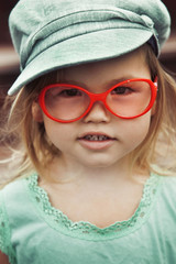 Little girl in red glasses and a cap