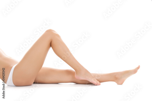 beautiful female legs barefoot lying on white background