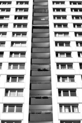 The facade of a multistory building. Black and white.