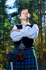 Man in scottish costume with sword and pipe