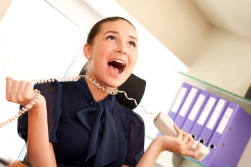Business woman screaming in telephone receiver