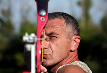 Portrait of professional bowman aiming with bow and arrow