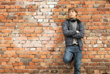 young man with headphones leaning on bricks wall