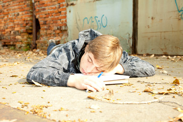 sleeping male student learning in the park