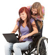 invalid girl on the wheelchair with laptop and friend