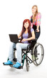 invalid girl on the wheelchair with laptop and helper